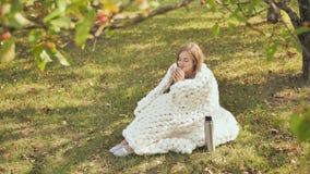 Una ragazza avvolta in un plaid merino è riscaldata da tè da una tazza del termos che si siede sull'erba in un parco della città video d archivio