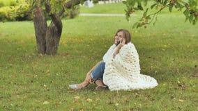 Una ragazza avvolta in un plaid merino che parla sul telefono che si siede sull'erba in un parco della città video d archivio