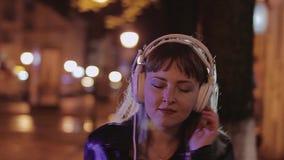 Una ragazza balla alla notte nella via alla bella luce Lampadina stock footage