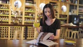 Una ragazza beve il caffè e legge una rivista di moda in un caffè o in un ristorante, la rivista della lettura della donna e bere stock footage