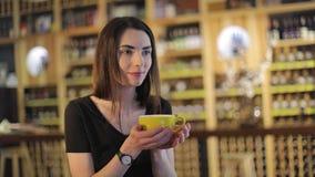 Una ragazza beve il caffè e legge una rivista di moda in un caffè o in un ristorante, la rivista della lettura della donna e bere video d archivio