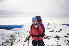 Una ragazza beve l'acqua alla cima delle alte montagne Immagini Stock