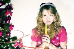 Una ragazza bionda che prega all'albero di Natale fotografia stock