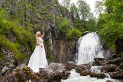 Una ragazza bionda giovane in una posa elegante getta sul bordo di un vestito dal boudoir nelle montagne contro un innalzamento d immagine stock libera da diritti