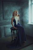 Una ragazza bionda in un vestito blu lussuoso immagine stock