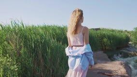 Una ragazza, bionda in un vestito rosa e camicia blu, sta con lei di nuovo alla macchina fotografica sulla riva rocciosa del fium video d archivio