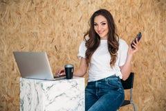 Una ragazza brillante con un sorriso dell'abbagliamento è vestita in abbigliamento casual che si siede su una sedia, lavorante pe Immagine Stock