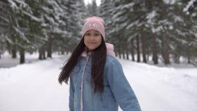 Una ragazza cammina attraverso una foresta dell'inverno con buoni nutrizione e turbinii intorno a se stessa Movimento lento video d archivio