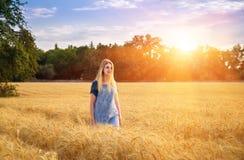 Una ragazza cammina attraverso un campo di grano maturo Immagini Stock