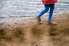Una ragazza cammina lungo l'acqua immagine stock libera da diritti