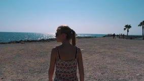 Una ragazza cammina lungo la linea costiera con le palme stock footage