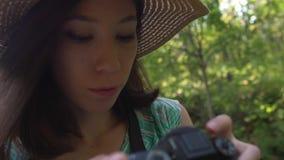 Una ragazza in cappello e vestito di paglia cammina attraverso il parco e fotografa la natura stock footage