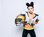 Una ragazza castana incredibilmente bella e atletica in shoulderpads e un casco di football americano che dimostra stordimento fotografia stock
