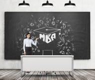 Una ragazza castana presenta lo schizzo di MBA sul bordo di gesso nero in un'aula moderna Tre plafoniere nere, pavimento di legno Fotografia Stock