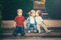 Una ragazza caucasica bianca adorabile divertente sveglia di tre dei bambini ragazzi dei bambini che si siede insieme baciandosi fotografie stock libere da diritti