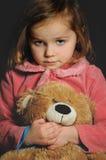 Una ragazza che abbraccia il suo orsacchiotto Immagine Stock Libera da Diritti