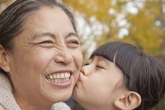 Una ragazza che bacia sua nonna, sorridente Immagine Stock Libera da Diritti