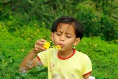 Una ragazza che dissipa le bolle Fotografie Stock
