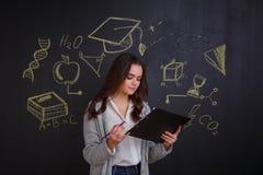 Una ragazza che esamina una cartella nera, stante accanto ad una lavagna con un'immagine di scienza e di conoscenza Immagini Stock