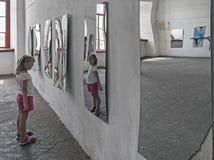 Una ragazza che esamina la sua immagine nello specchio distorto nel corridoio degli specchi immagini stock libere da diritti