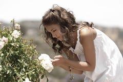 Una ragazza che esamina un fiore. Fotografia Stock Libera da Diritti