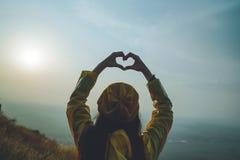 Una ragazza che fa simbolo del cuore con le sue mani al tramonto fotografie stock libere da diritti