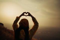 Una ragazza che fa simbolo del cuore con le sue mani al tramonto immagine stock