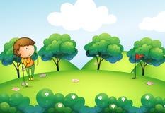 Una ragazza che gioca golf alla cima della collina Immagini Stock