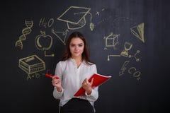 Una ragazza che giudica una cartella e un indicatore, stanti accanto ad una lavagna con le immagini delle scienze Fotografia Stock Libera da Diritti