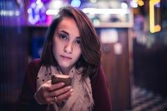 Una ragazza che guarda alla macchina fotografica facendo uso del vostro cellulare fotografia stock