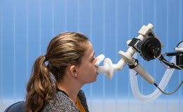 Una ragazza che ha una prova di funzione polmonare immagine stock