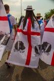Una ragazza che indossa una bandiera della Sardegna in un parco in pieno della gente immagine stock