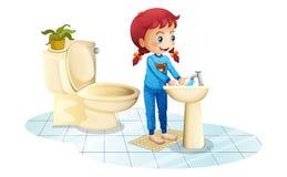 Una ragazza che indossa gli indumenti da notte blu che lavano le sue mani Immagine Stock