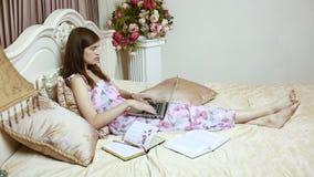 Una ragazza che lavora al computer a letto Reti sociali stock footage