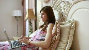 Una ragazza che lavora al computer a letto Reti sociali archivi video