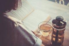 Una ragazza che legge un libro con una tazza di tè e la teiera sulla tavola dentro Immagini Stock