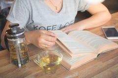 Una ragazza che legge un libro e che tiene una tazza della teiera di spirito del tè sui tum Fotografie Stock Libere da Diritti