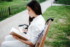 Una ragazza che legge un libro che si siede su un banco al tramonto Fotografie Stock Libere da Diritti