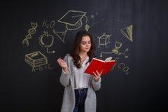 Una ragazza che legge un libro, stante accanto ad una lavagna con un'immagine di scienza e di conoscenza Immagine Stock Libera da Diritti