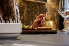 Una ragazza che mangia la sua pizza - tavolo da pranzo fotografie stock libere da diritti