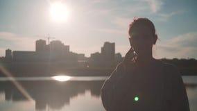 Una ragazza che parla su un telefono cellulare sul lago nei precedenti della città nei raggi del sole al tramonto stock footage
