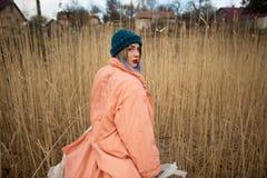 Una ragazza che porta un cappotto pastello e un cappello alla moda posa in un giacimento di grano Viev posteriore fotografia stock