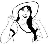 Una ragazza che prova su un cappello della spiaggia Fotografia Stock Libera da Diritti