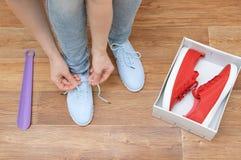 Una ragazza che prova sulle scarpe da tennis fotografia stock libera da diritti