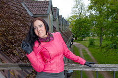 Una ragazza che si leva in piedi sul balcone Fotografie Stock