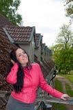 Una ragazza che si leva in piedi sul balcone Immagine Stock