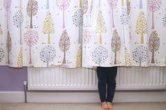 Una ragazza che si nasconde dietro le tende immagini stock