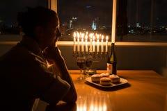 Una ragazza che si siede dalla finestra con il menorah che celebra Chanukah fotografie stock