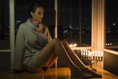 Una ragazza che si siede dalla finestra con il menorah che celebra Chanukah Immagini Stock Libere da Diritti