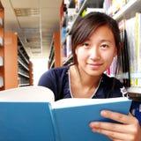 Una ragazza che si siede nella libreria Immagine Stock